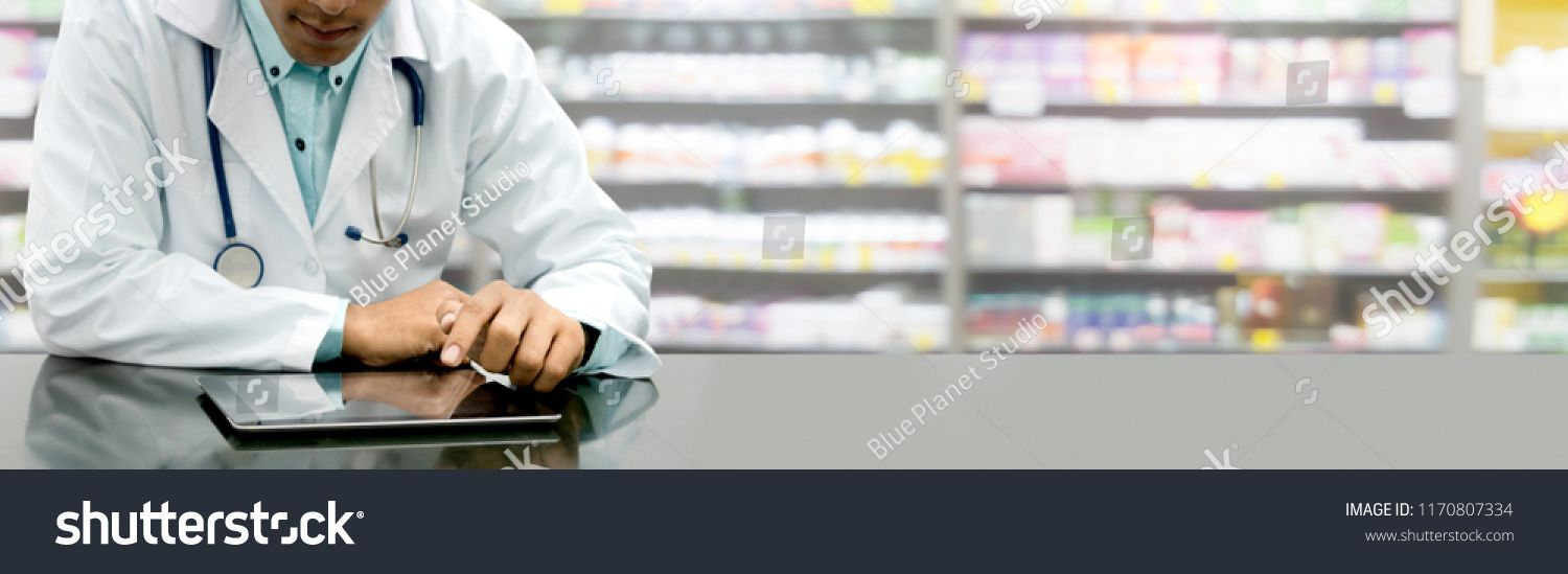 Male pharmacist sitting at table with tablet computer in pharmacy office. Medical healthcare staff and drugstore business. #Ad , #Ad, #table#tablet#computer#Male