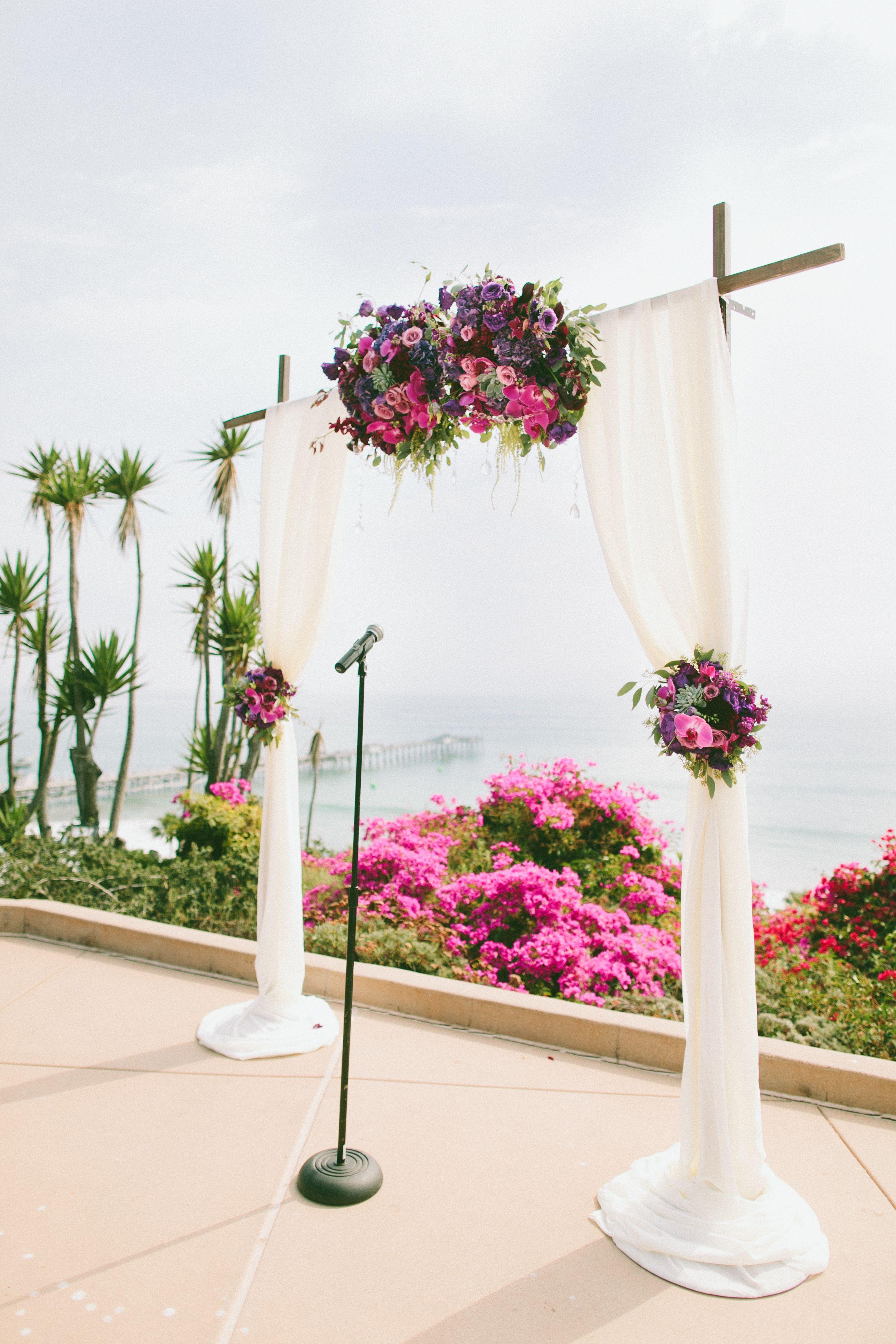 Ceremony wedding arc- Purple flowers and draping fabric. Casa ...