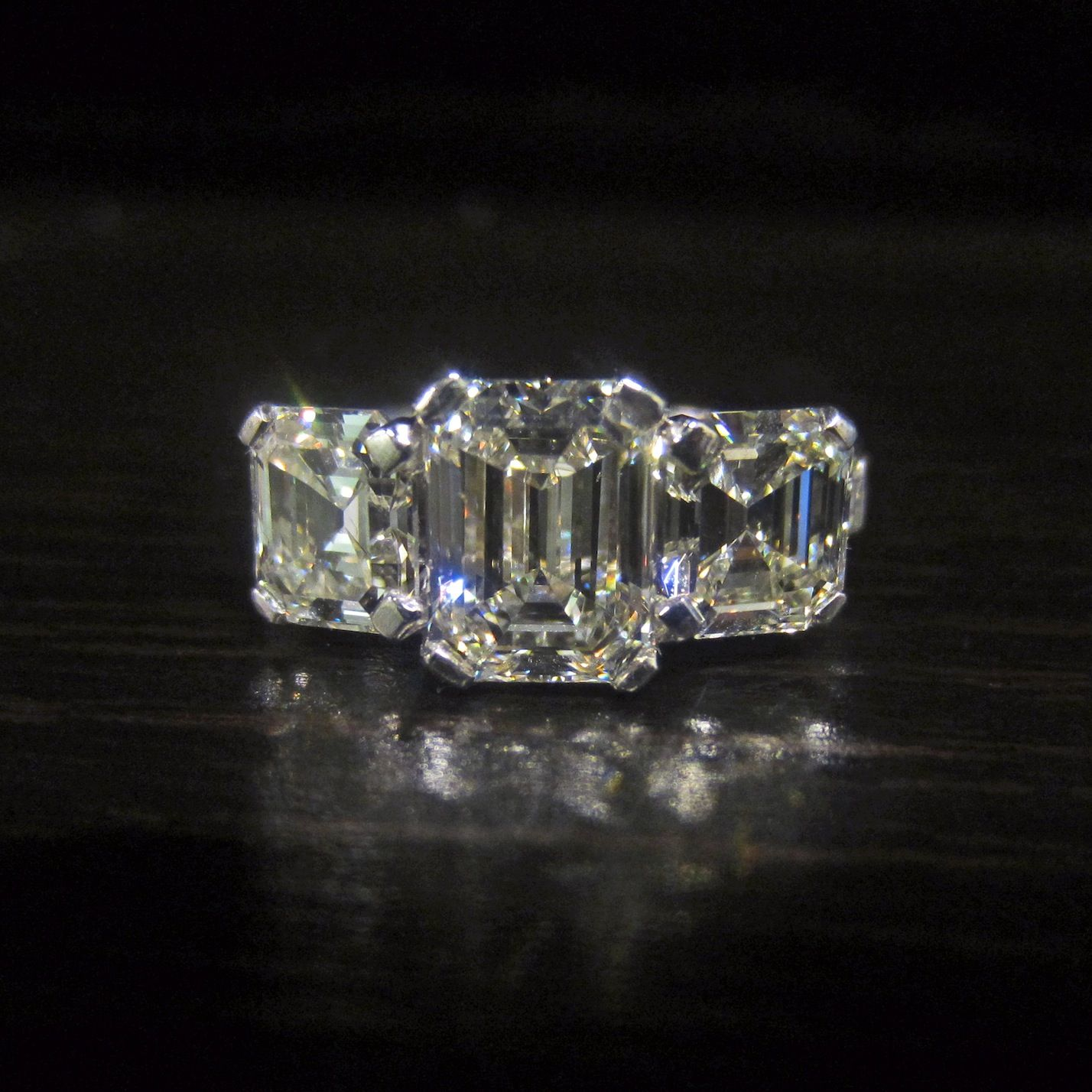 For the gal who wants serious sparkle, a contemporary three stone engagement ring in platinum, an emerald cut diamond flanked by Asschers. From Doyle & Doyle.