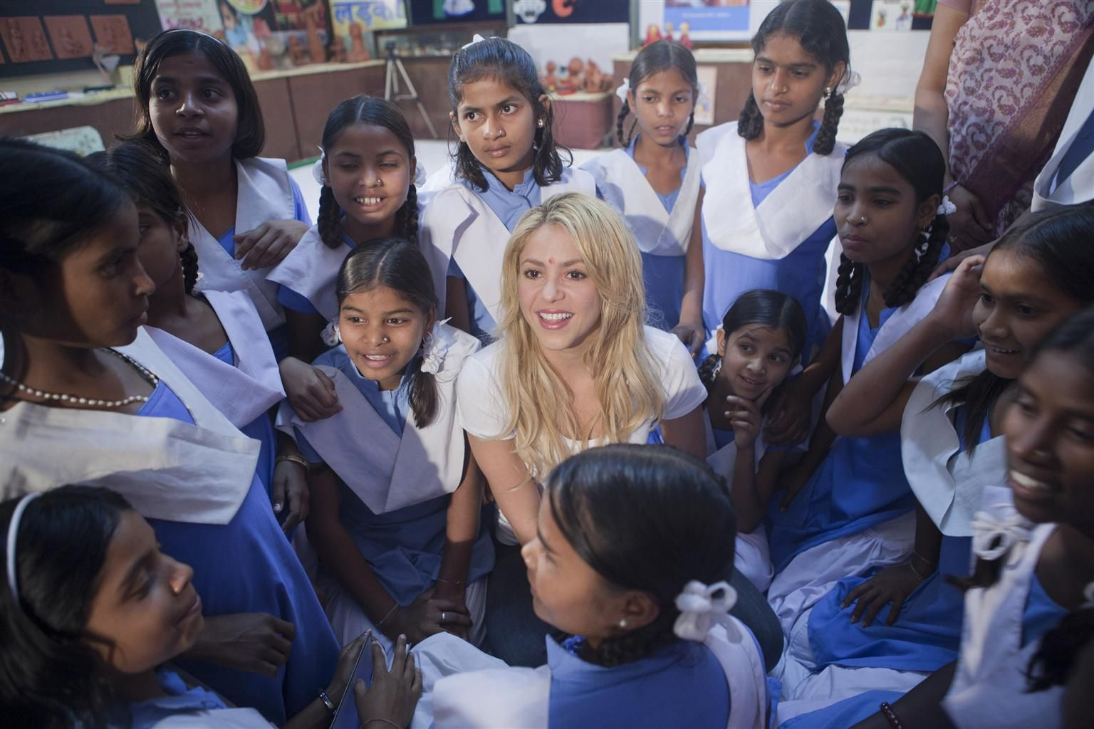 UNICEF Goodwill Ambassador Shakira smiles, sitting amidst adolescent girls from the UNICEF supported KGBV residential educational programme, in Udaipur District, India. Shakira met to discuss the importance of educating and empowering girls to break the cycle of poverty and inequity.  KGBV is a residential programme that provides a basic education and life-skills training for girls in marginalized and often difficult-to-reach areas. © UNICEF/Prashanth Vishwanathan http://www.unicef.org