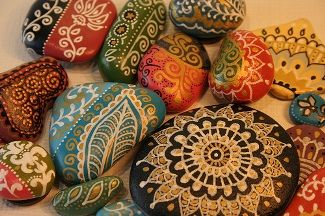 """Cut out a paper napkin design, place on pebble and brush with decoupage glue....I'm not sure """"why"""" but they are beautiful!!"""