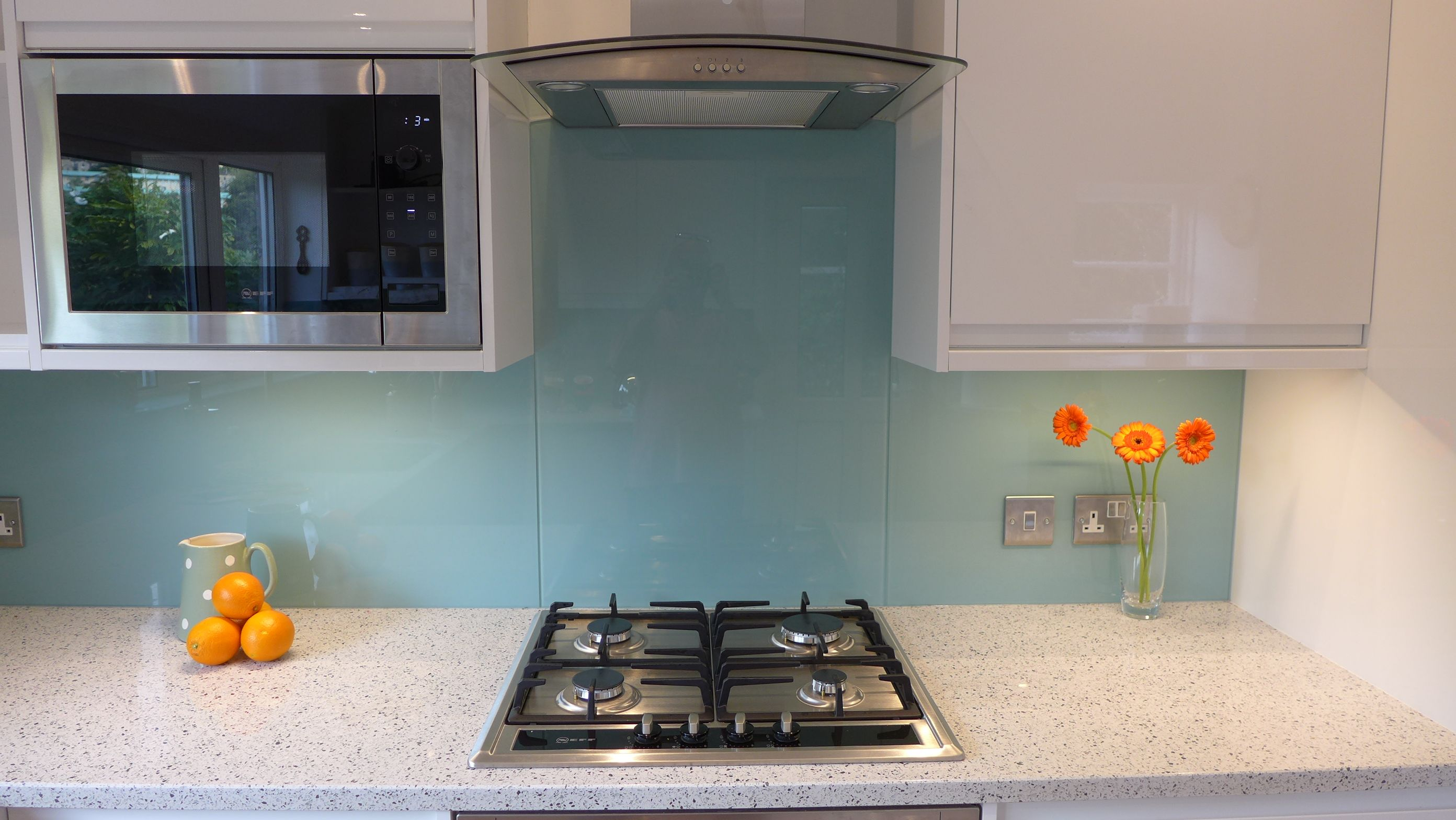 Blue kitchen glass splashback behind gas hob. See built-in microwave ...