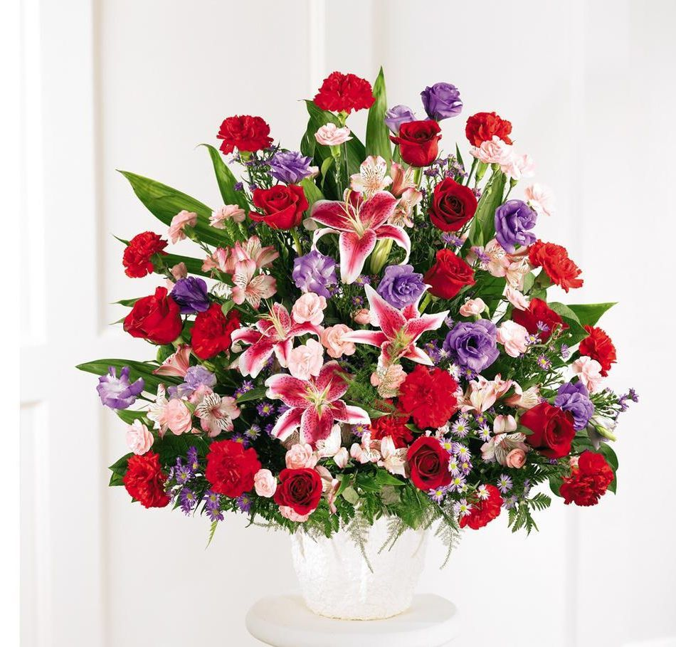 An abundance of stargazer lilies red roses and carnations