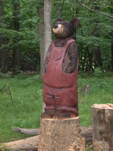 Tree stump carving indiana bear in coveralls chain saw