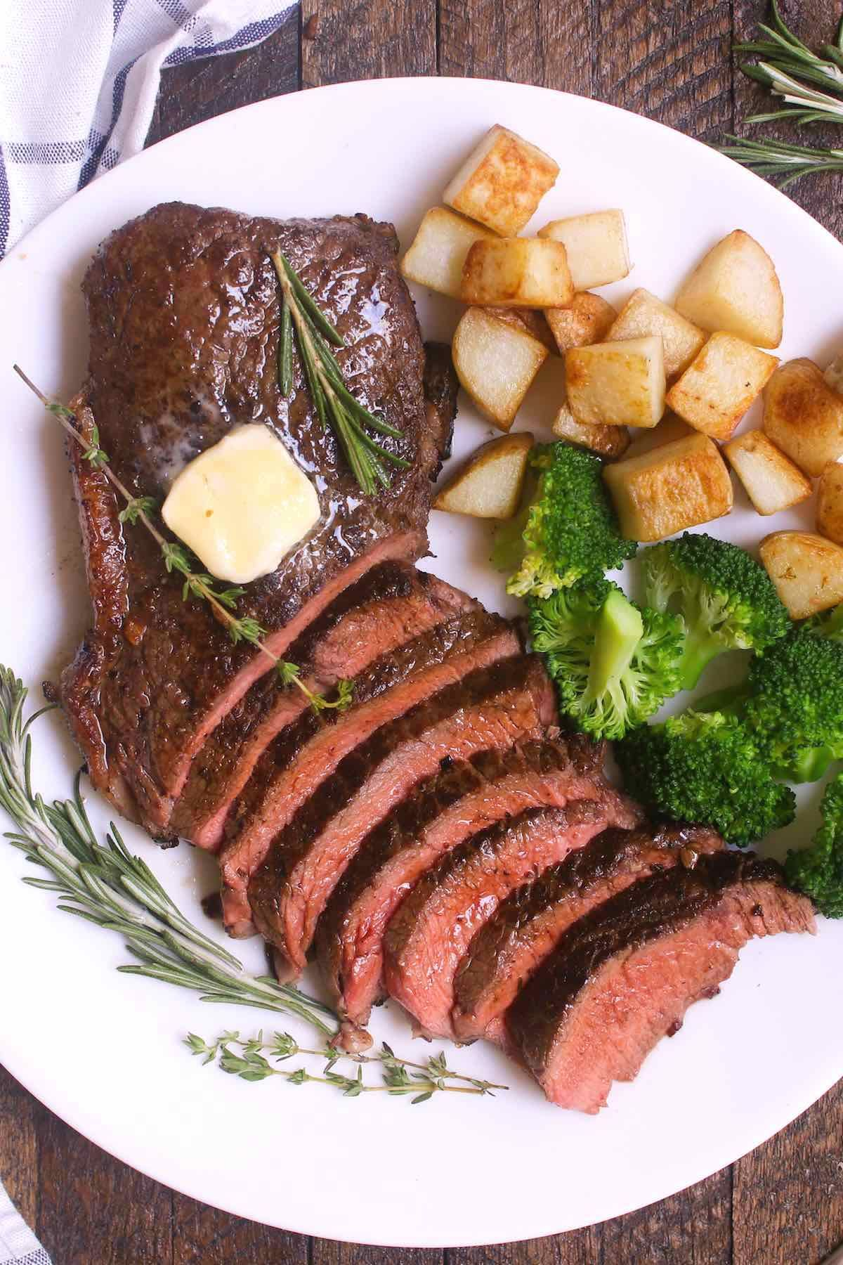 Overhead View Of A Sirloin Steak Dinner Consisting Of Sliced Top Sirloin Garnished With Fresh Rosemary Thym Steak Dinner Sirloin Steak Recipes Sirloin Recipes