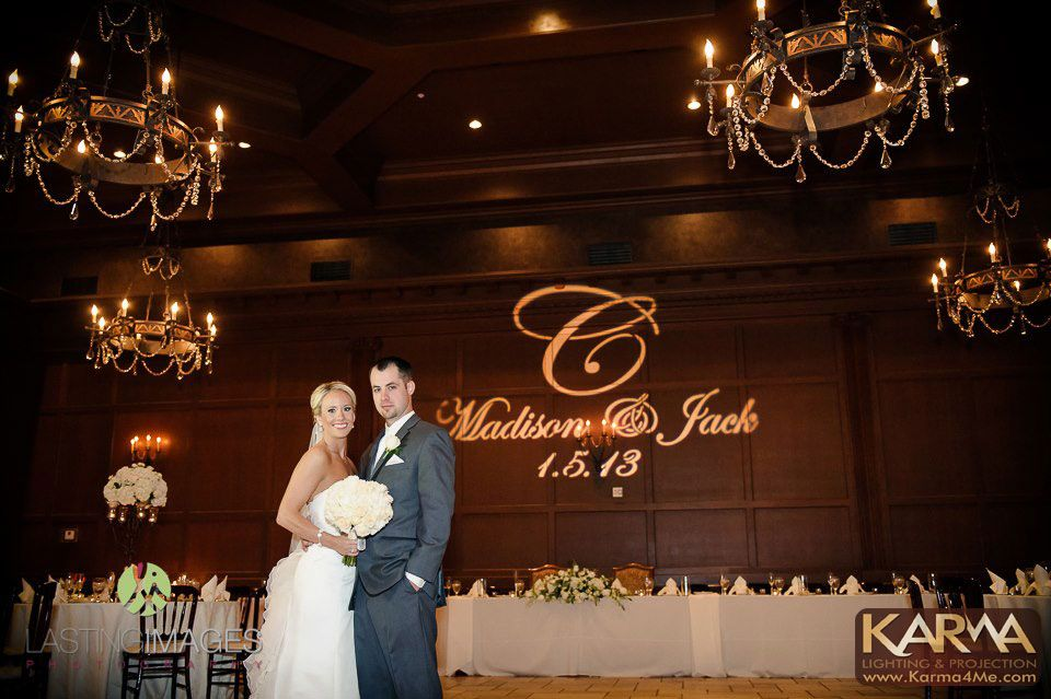 bride and groom with name and initials projected on wall behind them wedding gobo