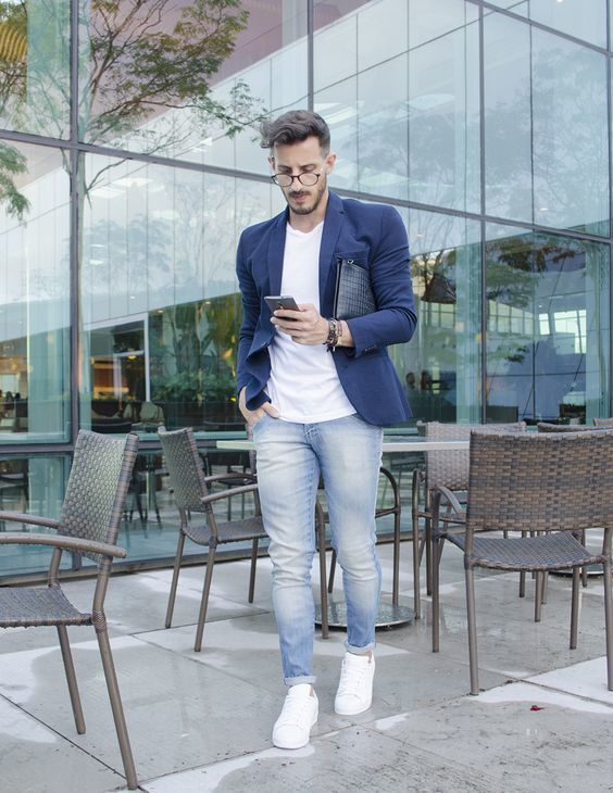 c2681508971 Pairing a navy blue blazer with baby blue jeans is an on-point option for a  day in the office. A pair of white leather low top sneakers brings the ...