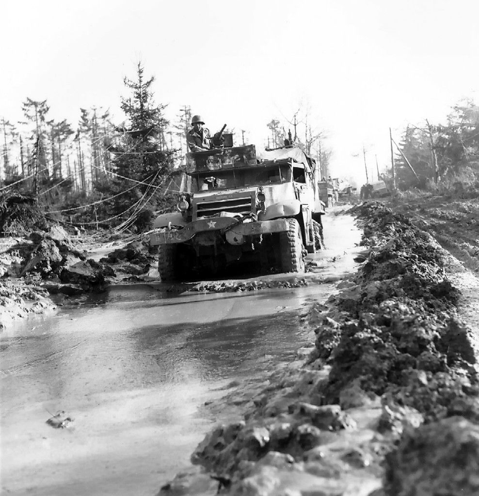 M3 Half-track vehicle of 16th Infantry Regiment, US 1st Infantry Division moving through a muddy road in the Hürtgen Forest, Germany, 15 Feb 1945.