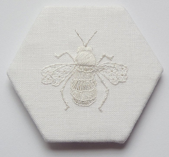 Ce charmant petit bourdon est travaillé en coton blanc et fil à