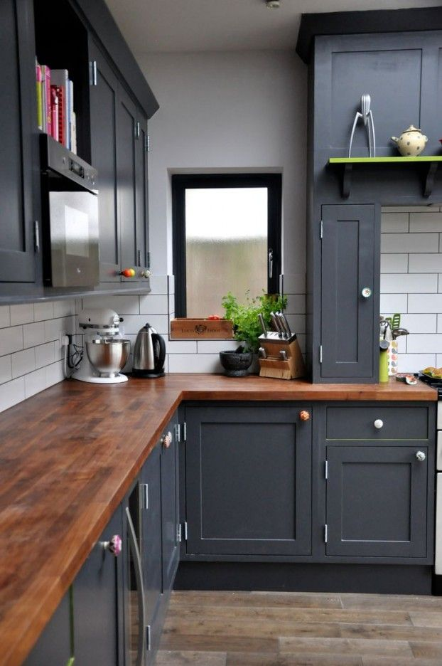 Dark grey cabinets, rich wood counter tops, white subway tile backsplash
