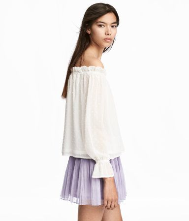 d2a6886f2e8 Natural white. Off-the-shoulder blouse in plumeti chiffon with elasticized  trim at top and long sleeves with elasticized, flounced cuffs. Rounded hem.