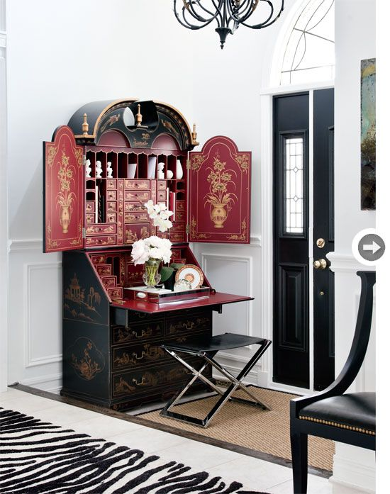 Black, red and gold chinoiserie secretary, sisal, leather and zebra-print rug, black door in the entry
