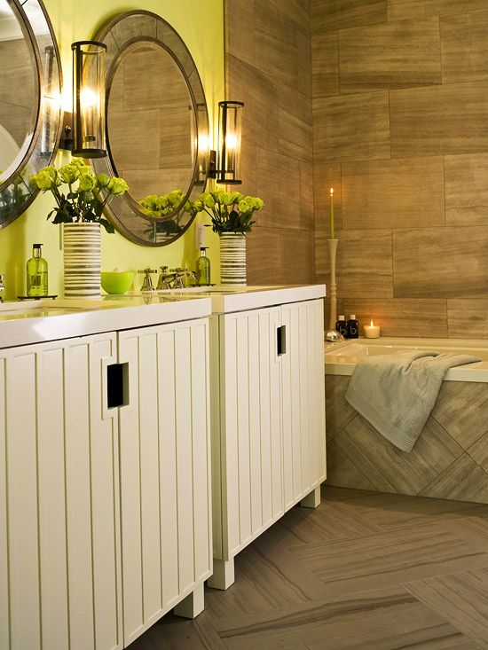 This almost-yellow shade of green is just enough color to add a signature style to this calming bath. The same striated tile is used from ceiling to floor for a continuous block of sandy brown color in this bathroom. A creamy tone was chosen for the lacquered vanities, as a pure white would have been too stark to pair with the other soothing elements./