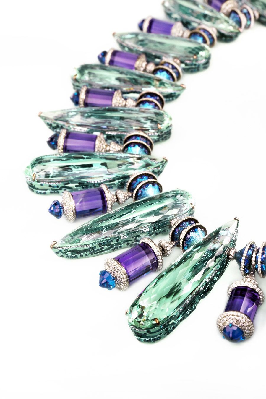 Wallace Chan Necklace of aquamarine, sapphires, amethyst and diamonds set in titanium. The settings of the aquamarine deserve special note, they are titanium shells, anodized to match the color of the stones nearly exactly and set with tiny diamonds, giving them the appearance of just sticking to the outside of the large stone unsupported.