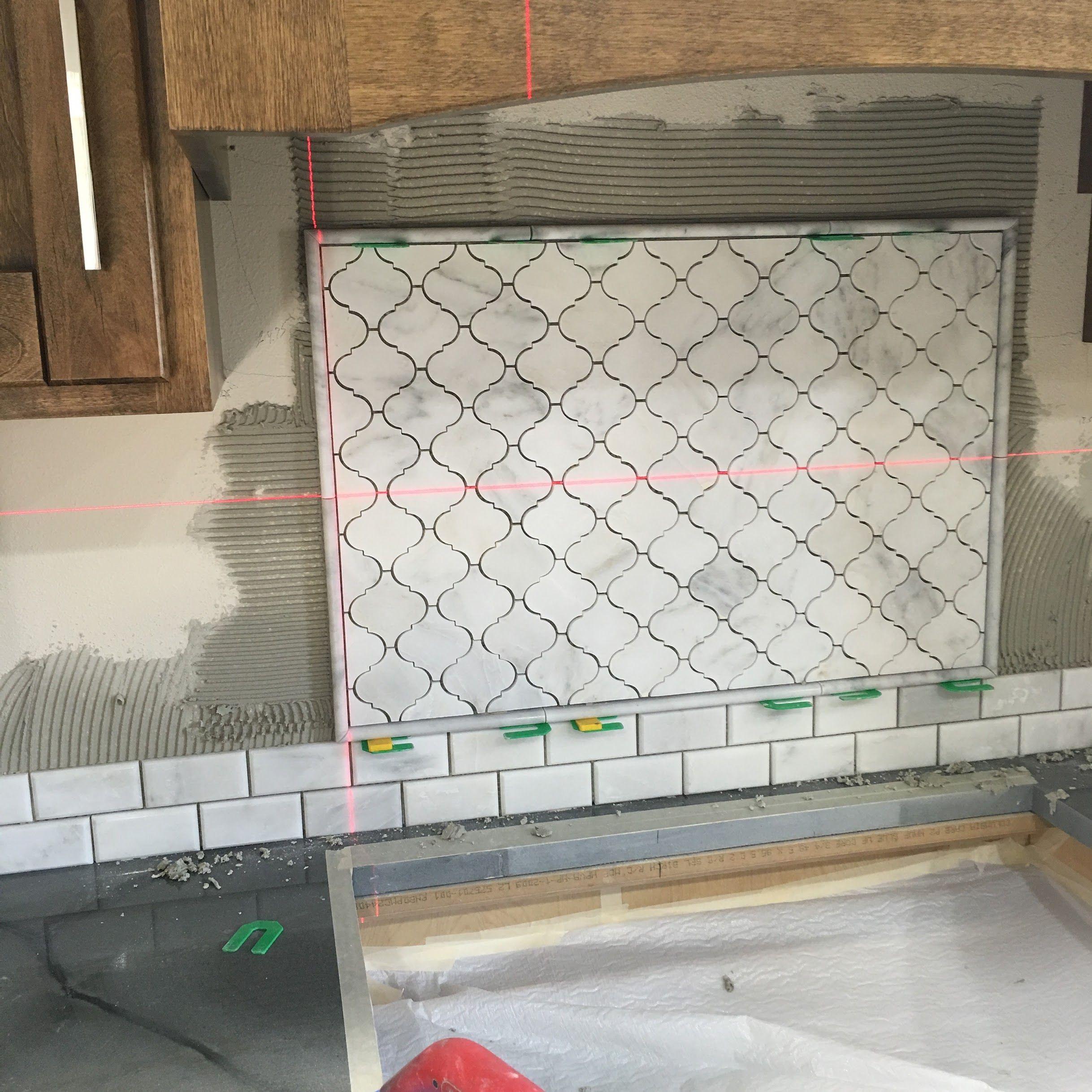 White marble kitchen backsplash 3 arabesque lantern inset above range venato carrara honed