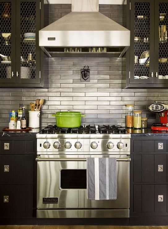 Contemporary kitchen features chicken wire upper cabinets and black