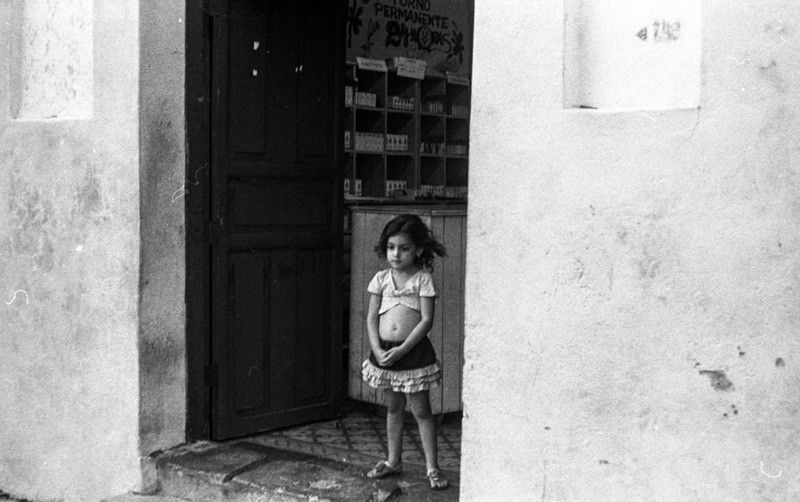 A girl stands at the door of a pharmacy in Cienfuegos, Cuba. Shot on my Leica M3 : Sergio Villalba - travel and sport photographer