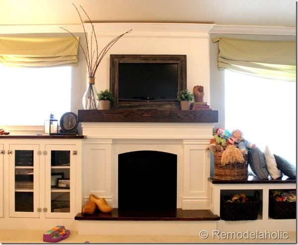 Note the framed flat screen tv mantle styled with wood