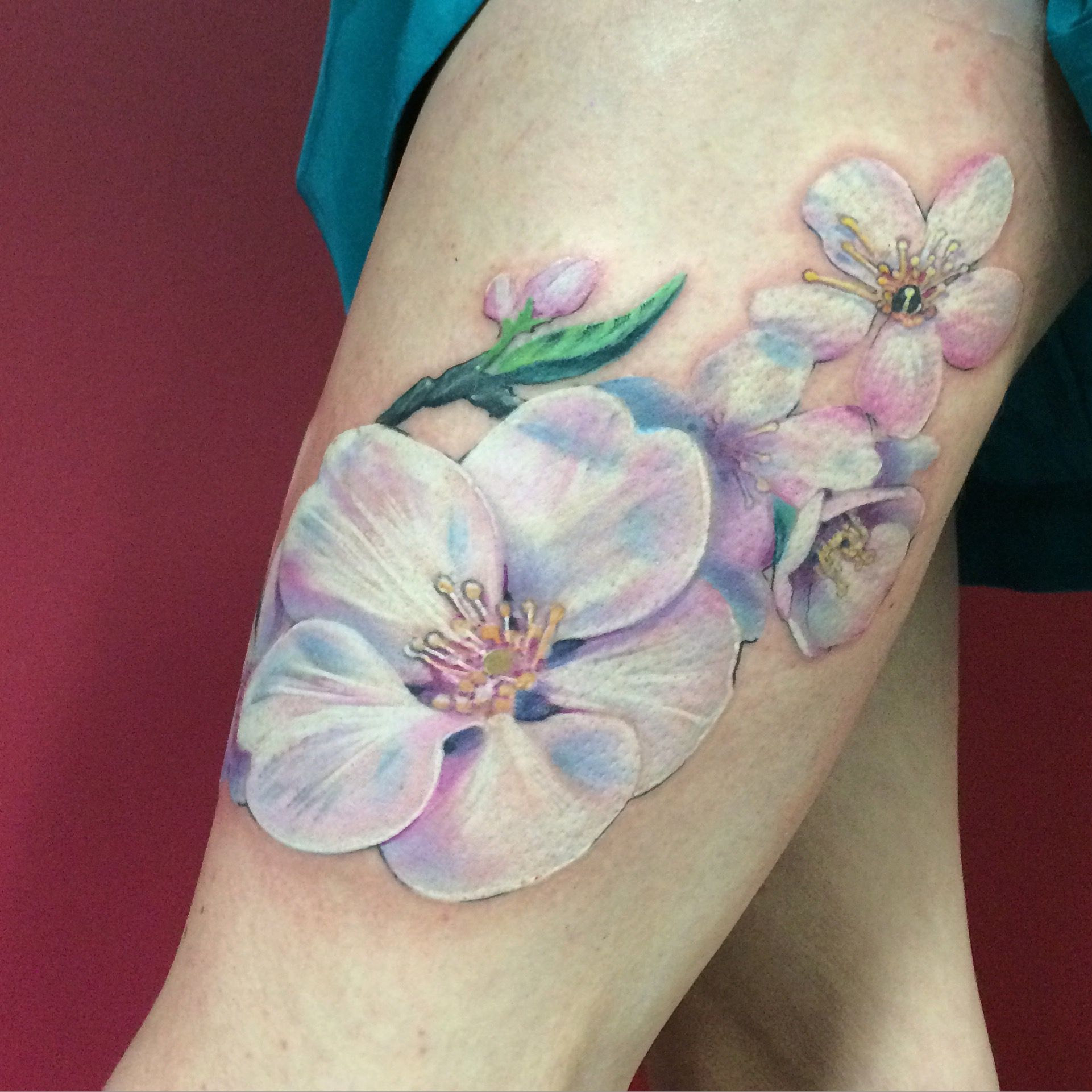 Lovely white and pastel flower tattoo by Nadine from