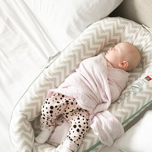 Blissfully napping in a DockATot Deluxe baby lounger.