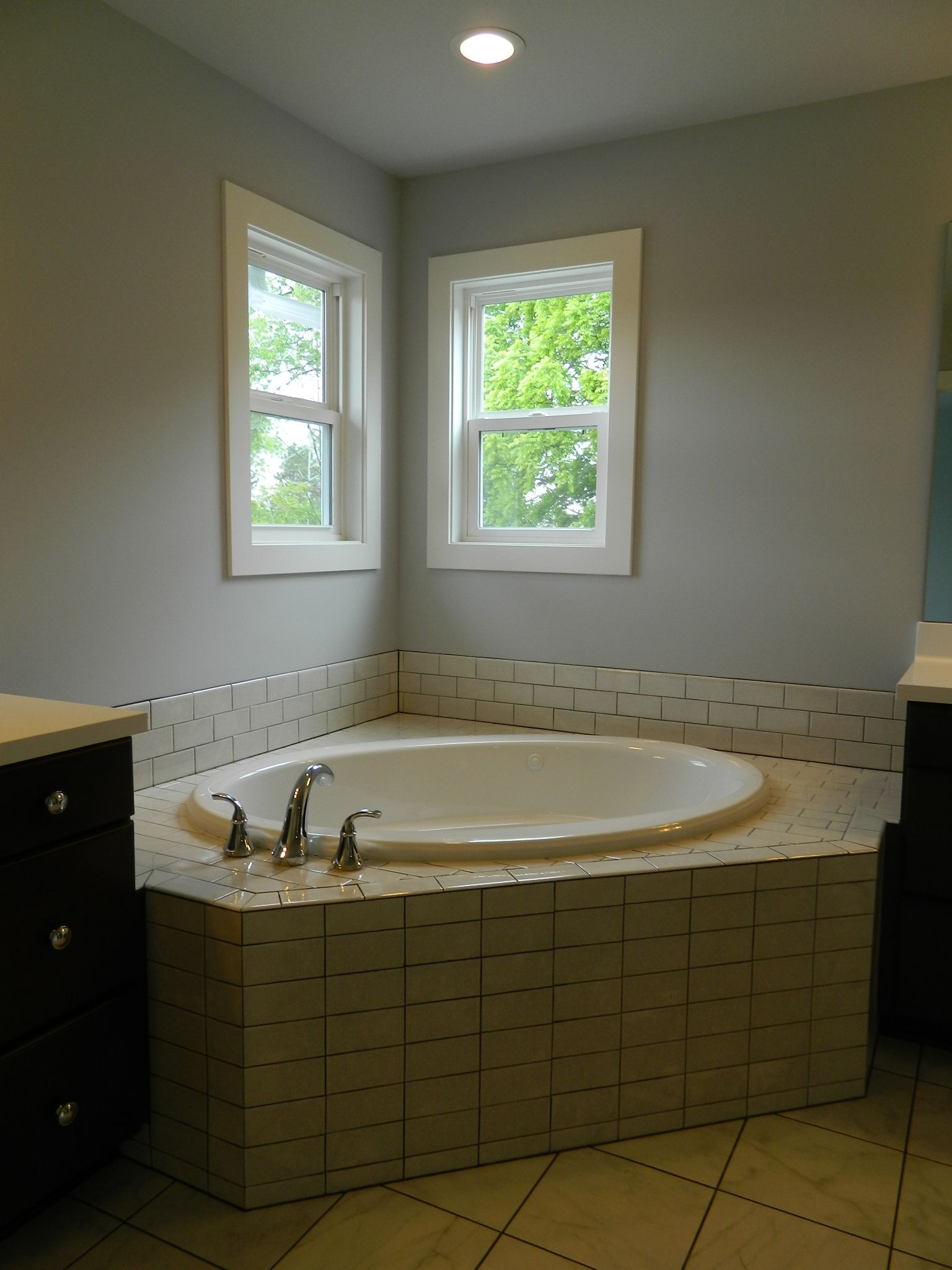 Subway tile tub deck with drop-in bathtub. Double-hung windows ...