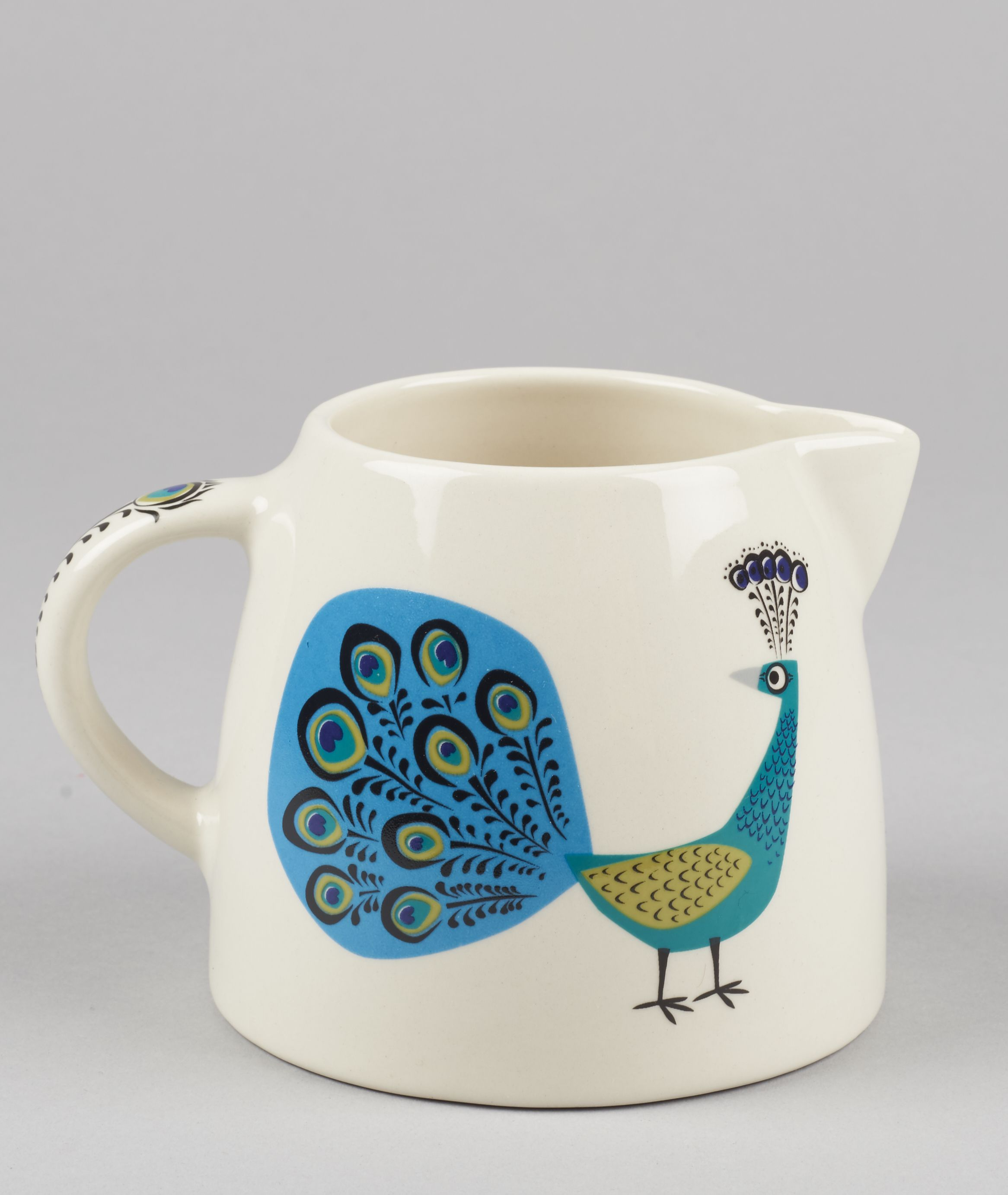 Hannah Turner Peacock Creamer Jug: The Hannah Turner peacock range is both elegant and stylish. Each product is handmade and embellished with beautifully illustrated designs of elegant strutting peacocks. This classically designed creamer jug has so many handy uses, a great practical addition for any cook or kitchen.  Hannah Turner started her business in 1991 after a sell out degree-show. Hannah works out of a studio based in the back garden of her home in Bristol, selling her amazing…