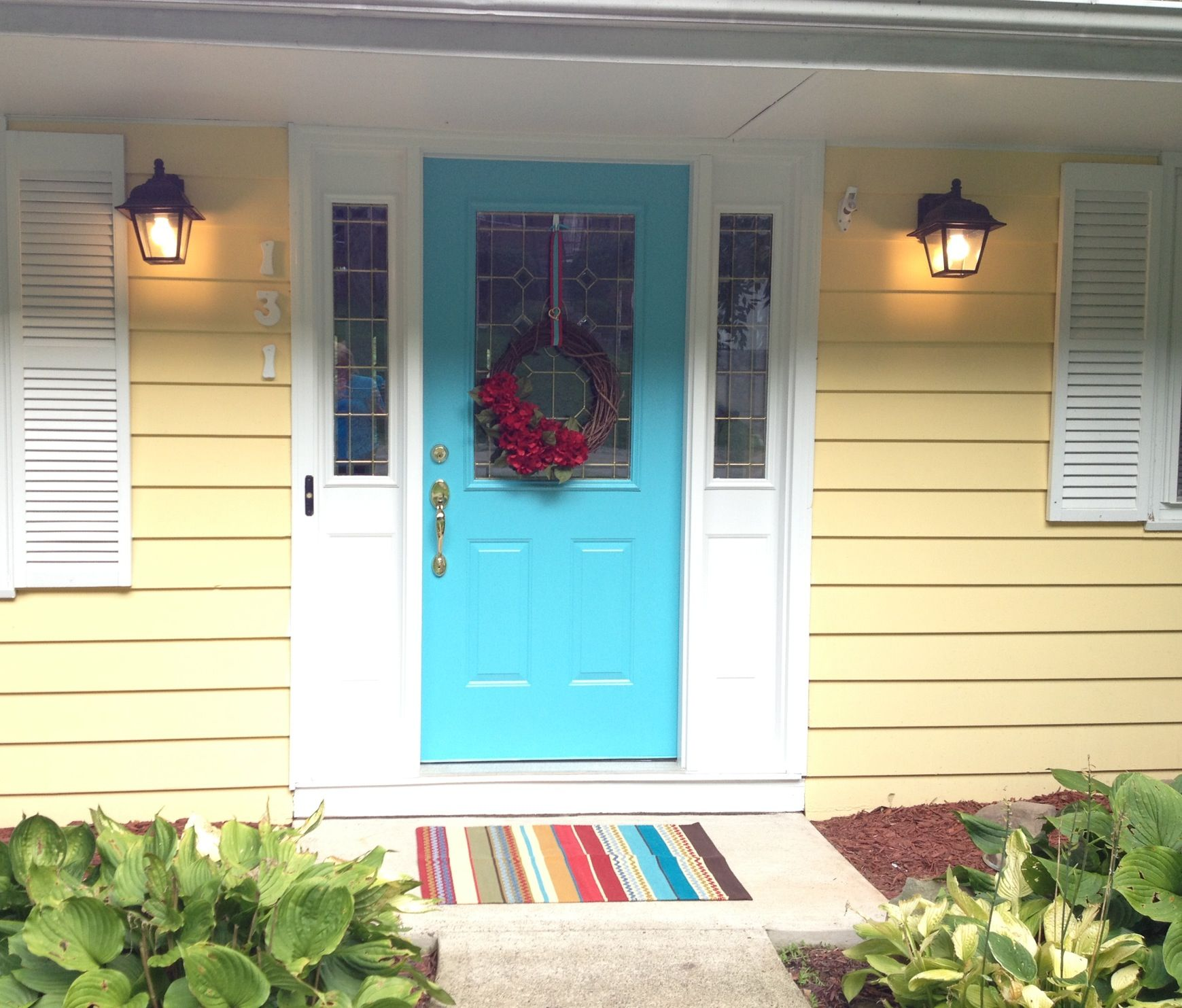 white front door yellow house. yellow siding white trim teal front door house