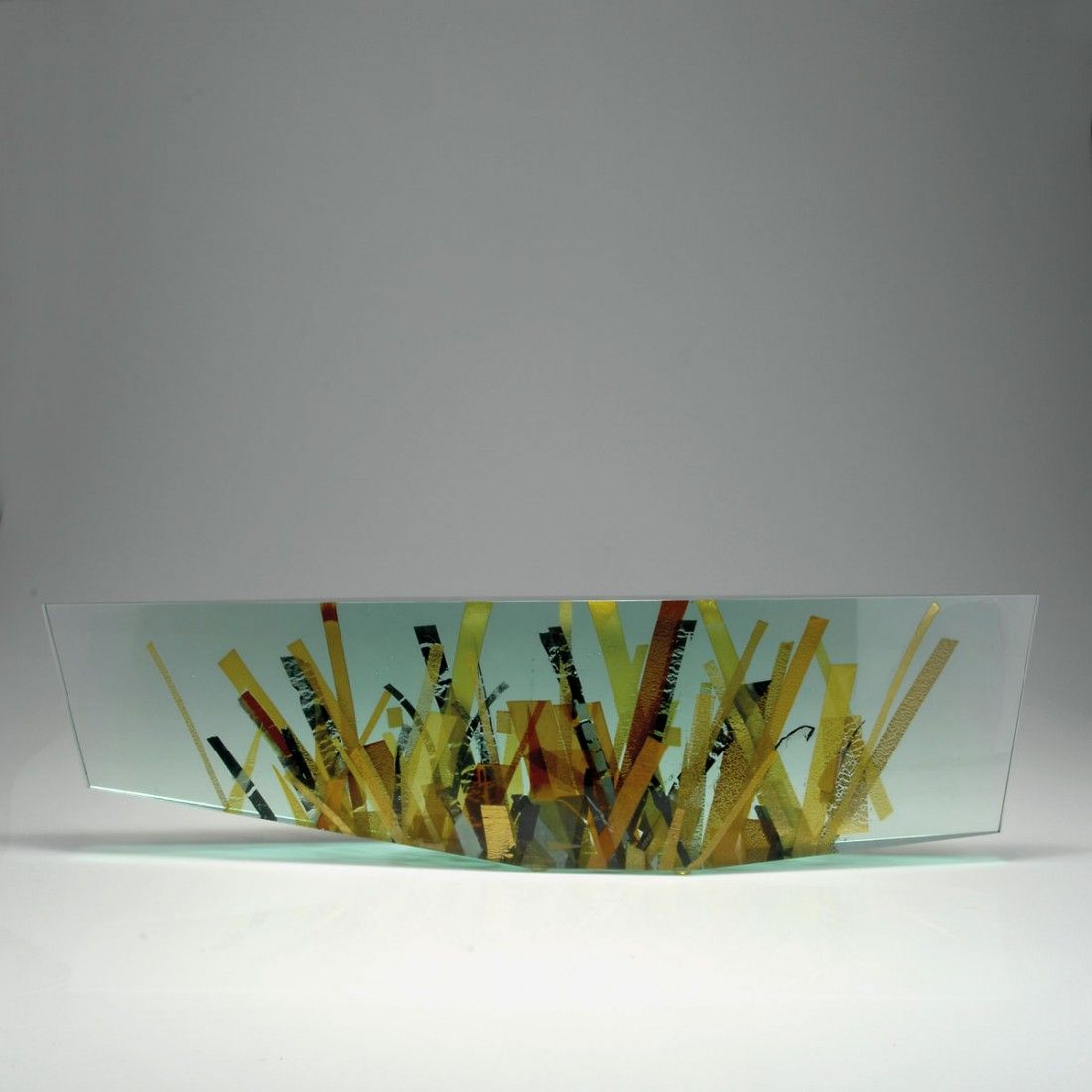 Tomas Hlavicka. Sculpture, 1999.  Clear glass block, cast and polished, included metal bands in gold, silver and bronze