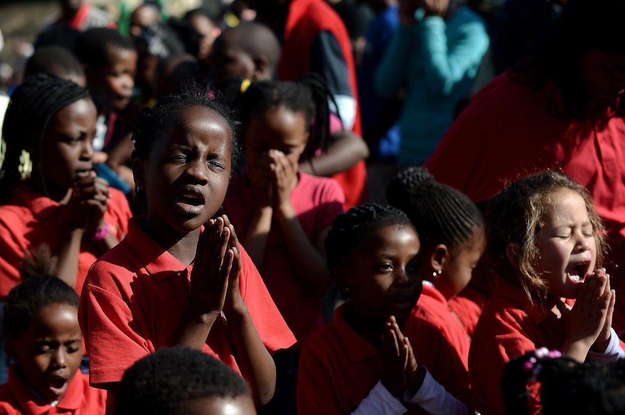 Los niños rezan delante de la Medi Clinic Heart Hospital en Pretoria. El presidente de Sudáfrica, Jacob Zuma, dijo que la condición de Nelson Mandela había mejorado durante la noche y ahora era crítico, pero estable. (AFP)