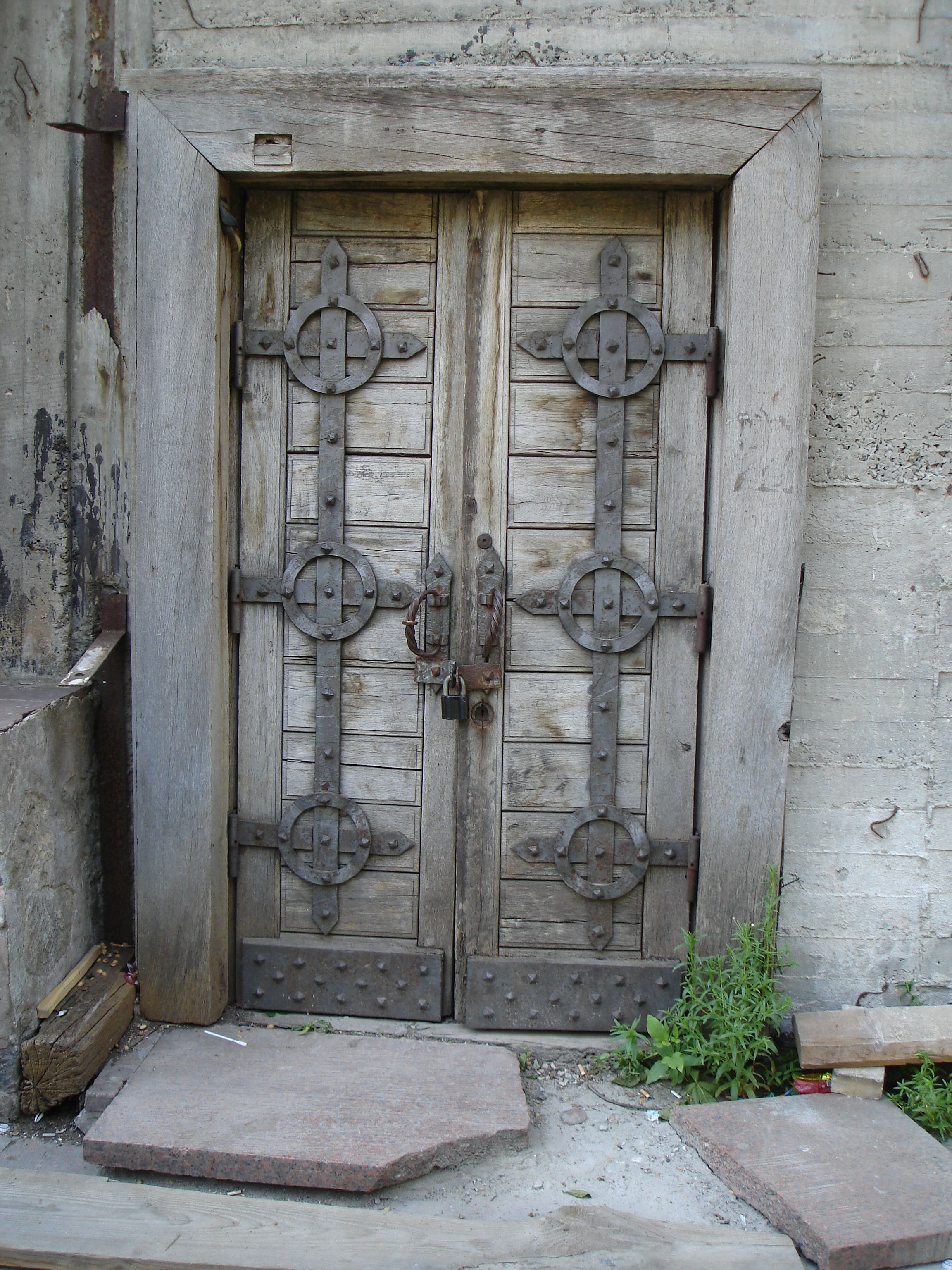 Very old wooden doors with metal hardware in stone ...