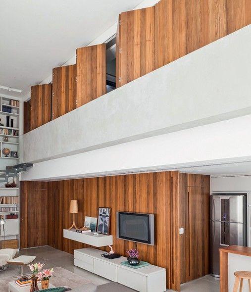 Um fechamento com painéis articulados de ipê-peroba com 1,23 m de altura garante que o quarto seja vista da sala de estar do apê com pé-direito duplo. Projeto do escritório RoccoVidal P W