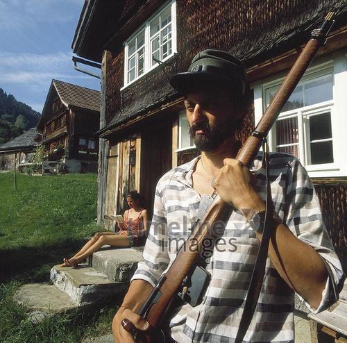 Mann und Frau vor einem Bauernhaus, 1986 relpel/Timeline Images #1980er #1980s #80er #80s #Gewehr #Waffe #Alpen #Schweiz #Schweizer #Waffen #Gewehre