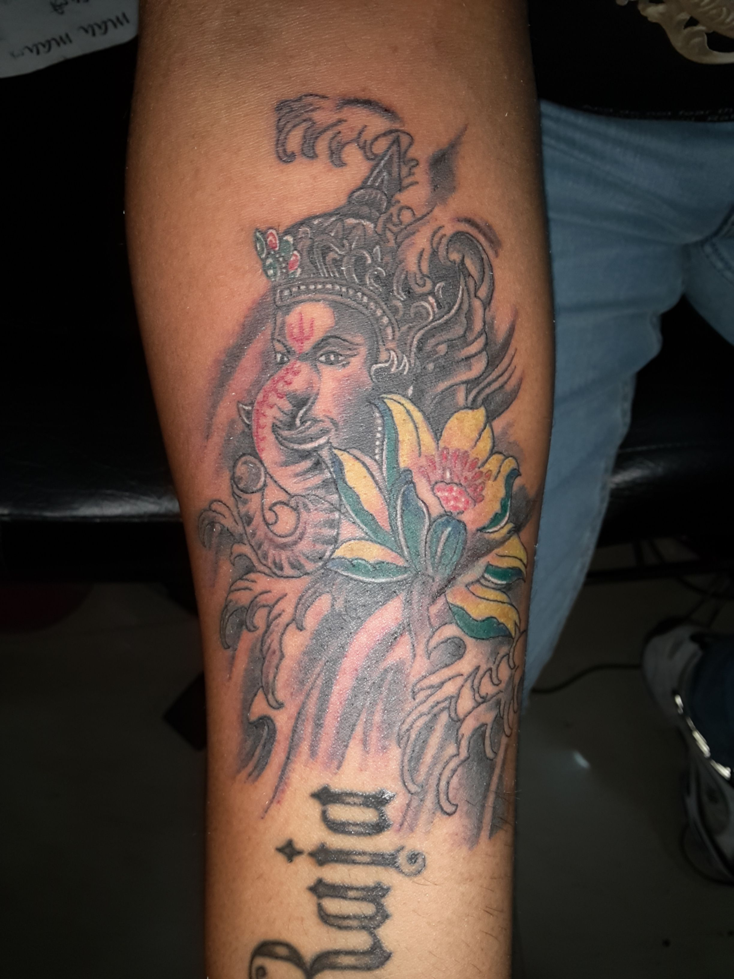 lord ganesha with flower at The art tattoo studio