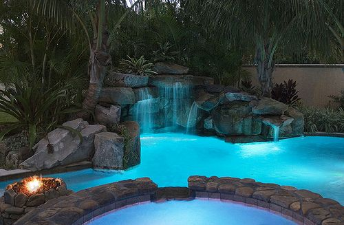 Stone Spa And Grotto Waterfall With Stone Fire Pit Lit Up Pool Waterfall Lagoon Pool Backyard Pool