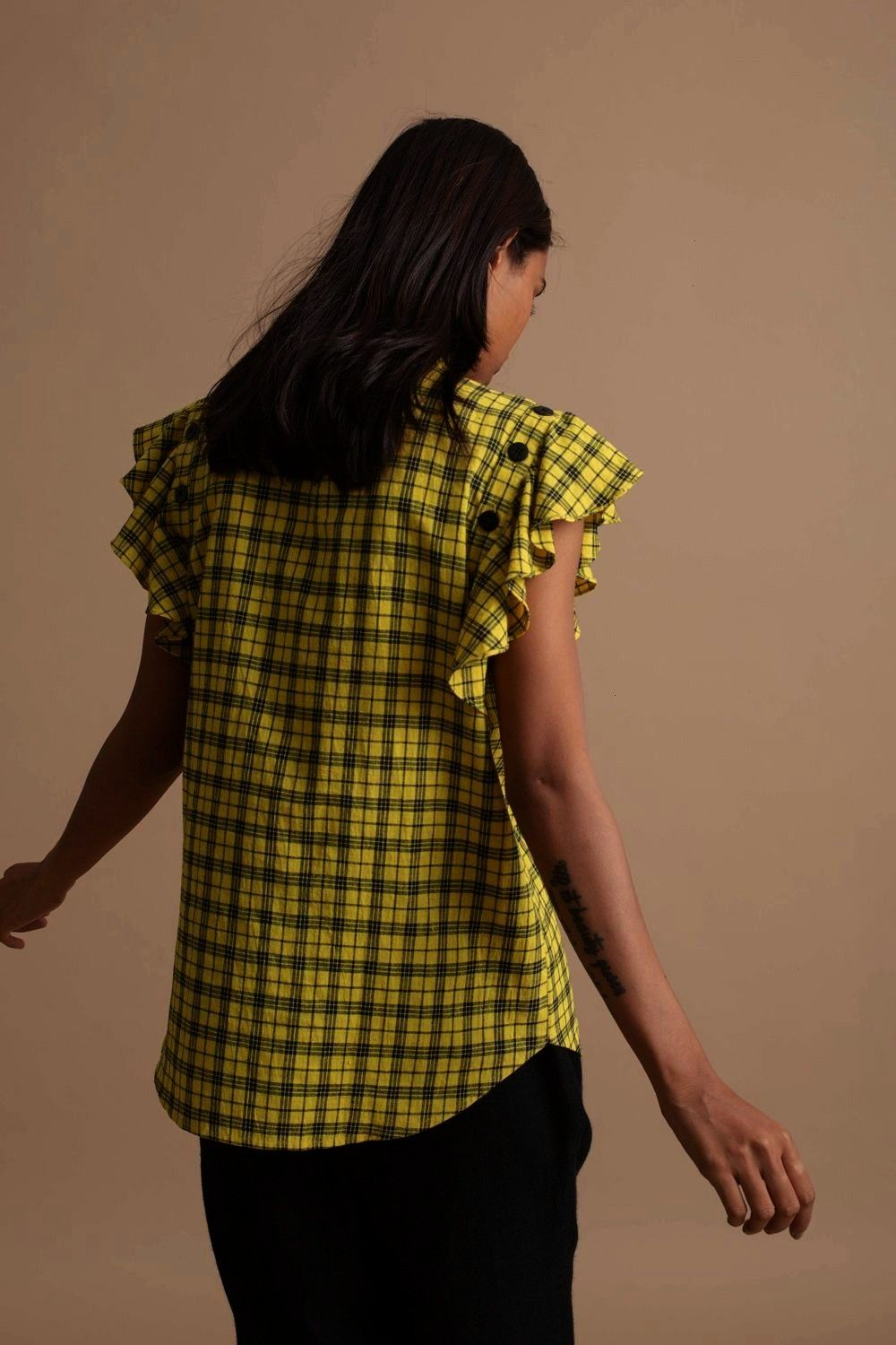 Top from Kanelle The Detachable Sleeve top is crafted from handspin cotton in a yellow and black checkered pattern The straight fit top comes with detachable frills that...