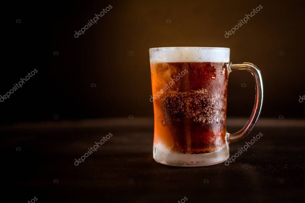 A cold glass of beer with dark brown background - Stock Photo ,