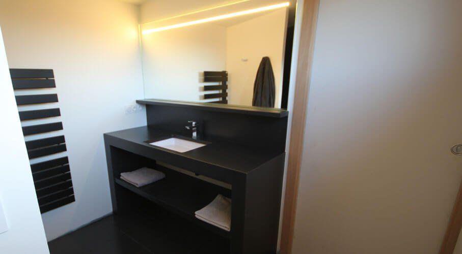Réalisé en béton ciré, ce meuble de salle de bains noir et blanc s