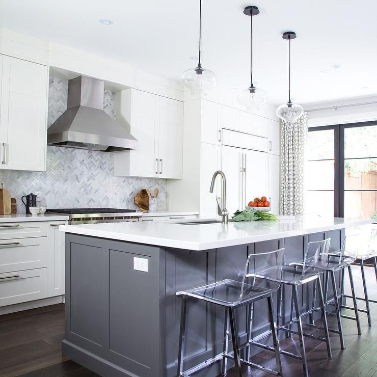 White Kitchen Cabinets With Gray Countertops: Three Clear Glass Island Pendants Hangs Over A Gray Center
