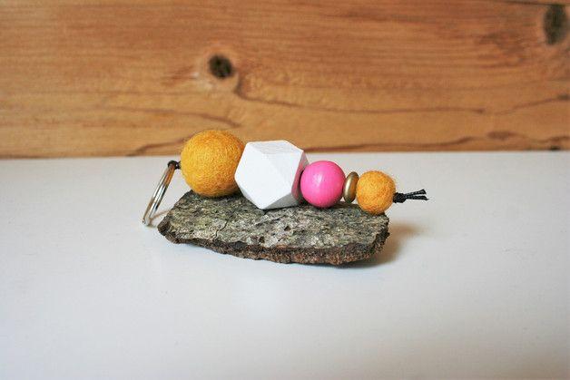 Schlüsselanhänger mit Filzkugeln in zwei unterschiedlichen Größen in Gelb (fast senfgelb), selbstbemalte und matt lackierte Holzperlen in weiß und rosa (in geometrischer und runder Form) und Holzlinse in goldfarben. Aufgefädelt auf eine schwarze Kordel. Dieser Schlüsselanhänger hat eine Länge von ca. 10,5 cm.