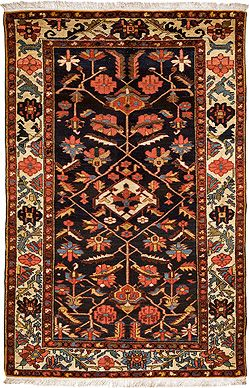 An old carpet woven in wool, the predominant color is the indigo dye. The deep blue field with stylized geometric overall floral motif is contrasted by fuschia pink. and the use of white enhaces the indigo  This carpet has been procured from the collection of the erstwhile Maharaja of Kashmir.