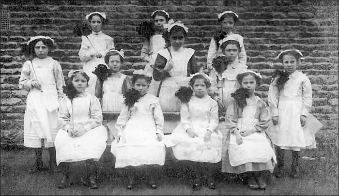In the early 1900's a group of girls are dressed ready to perform as maids in a school play.