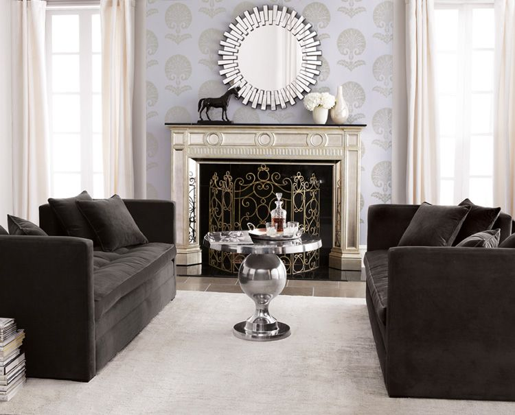 pewter grey settees, antiqued white mantel with mirrored insets, pale grey rug, polished recycled aluminum pedestal table, sunburst mirror, antiqued brass fire screen