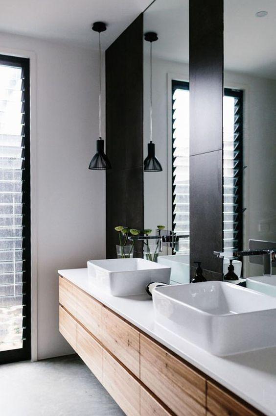 Los pequeños detalles en negro como las lámparas o el hueco entre espejos pueden llenar de personalidad tu baño
