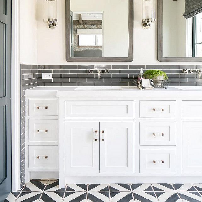 master bathroom featuring white cabinets wall faucets gray subway tile rustic framed mirrors and black and white cement floor tiles
