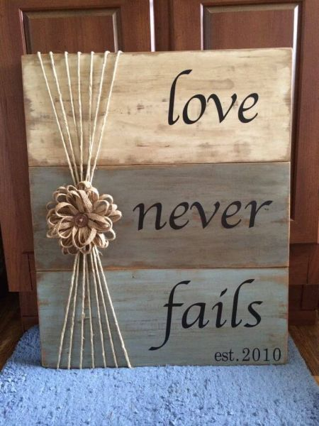 """Photo of """"Love Never Fails"""" Tri-Color Weathered Wood Sign"""