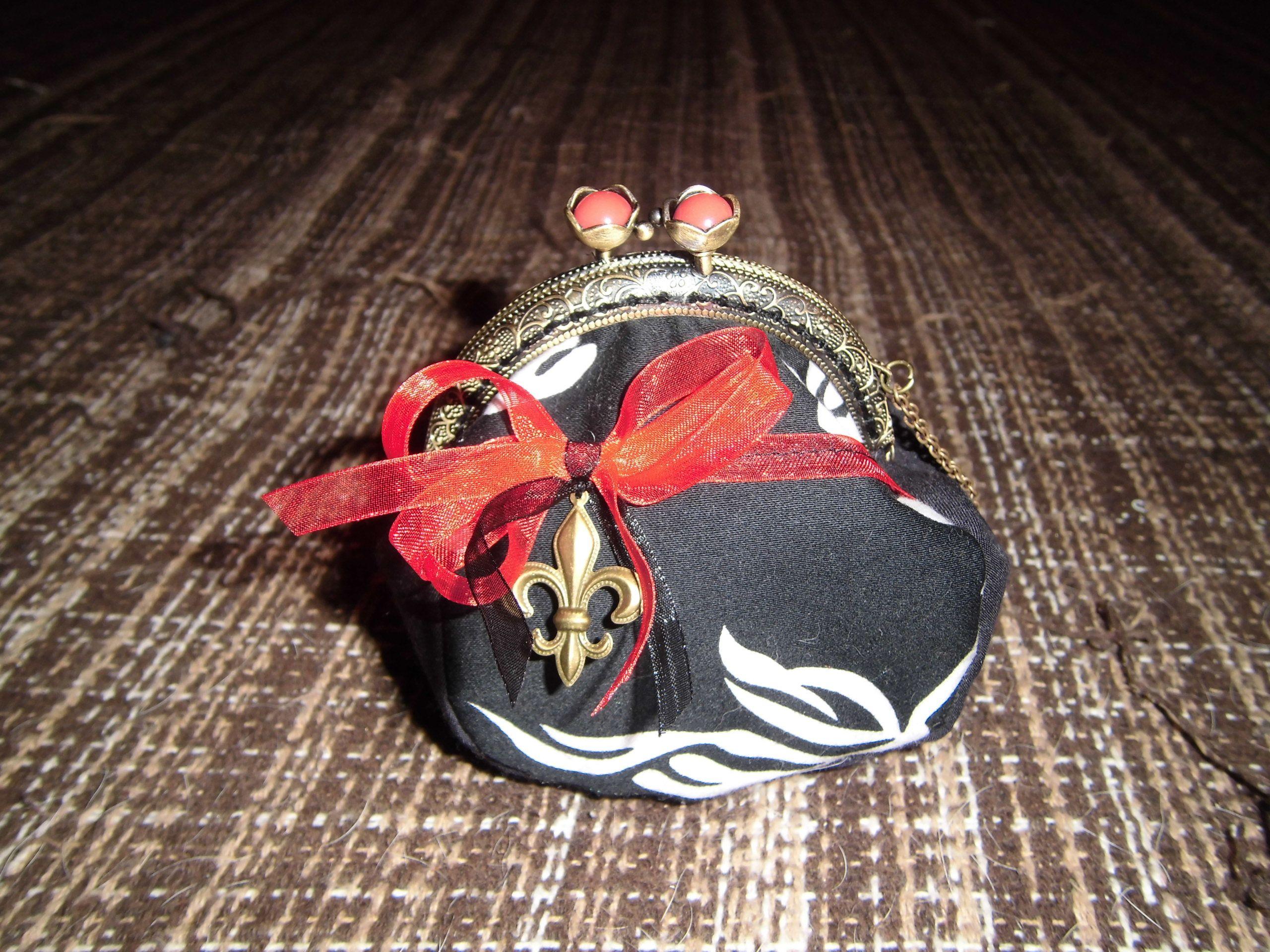 monedero blanco y negro con lazo rojo y flor de lis.