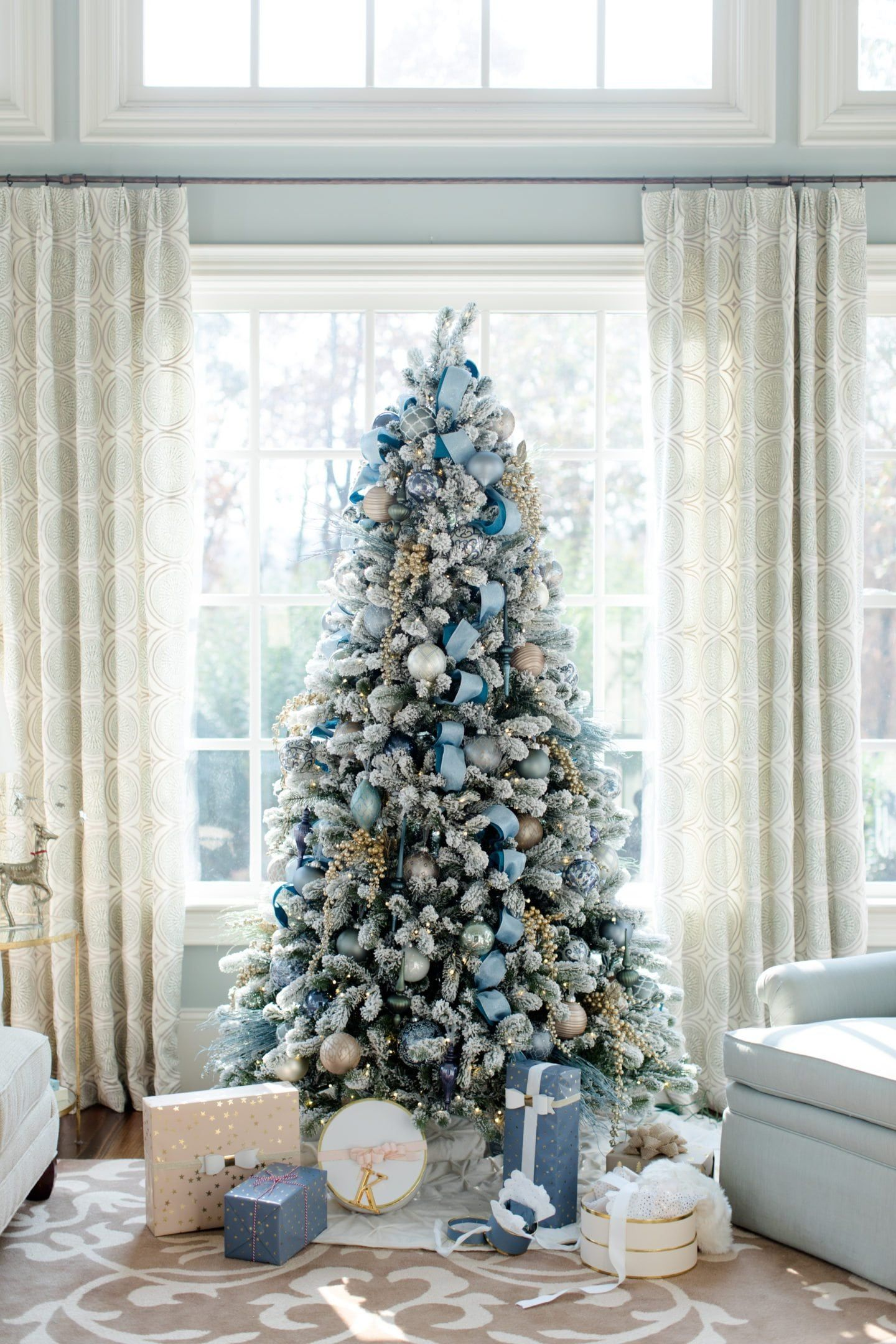 Flocked Christmas Tree With Blue Glornaments And Blue Ribbon And Presents Below It