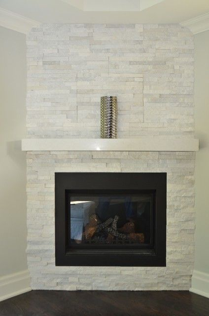 White Stone Fireplace With A Black Mantle In Place Of White