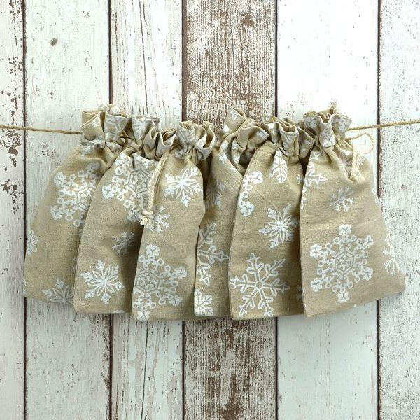 Set von sechs Leinenbeuteln mit hübschem Schneeflockendruck und Baumwollzugband.