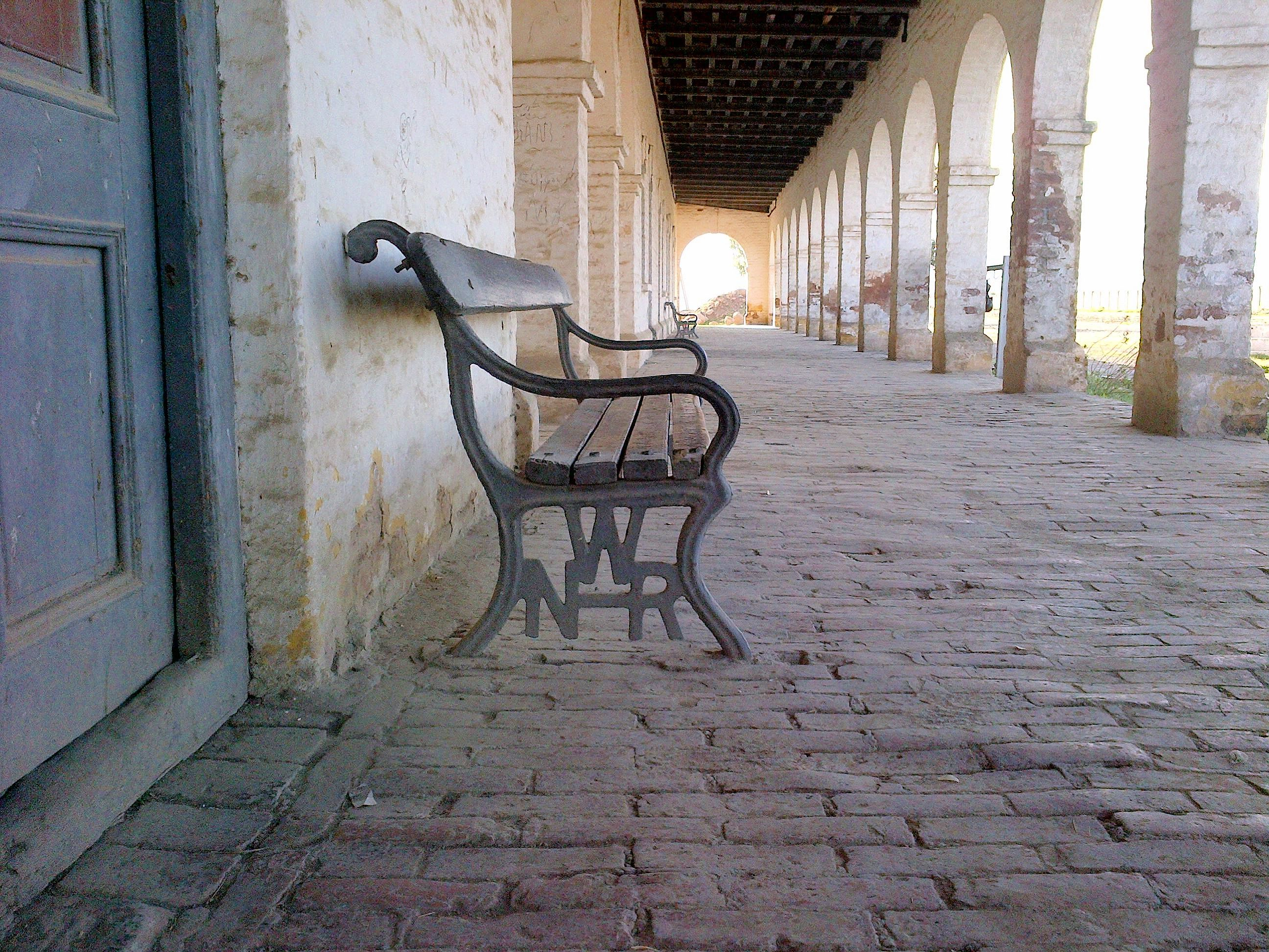 Waiting chair made of cast iron and timber planks. The ...